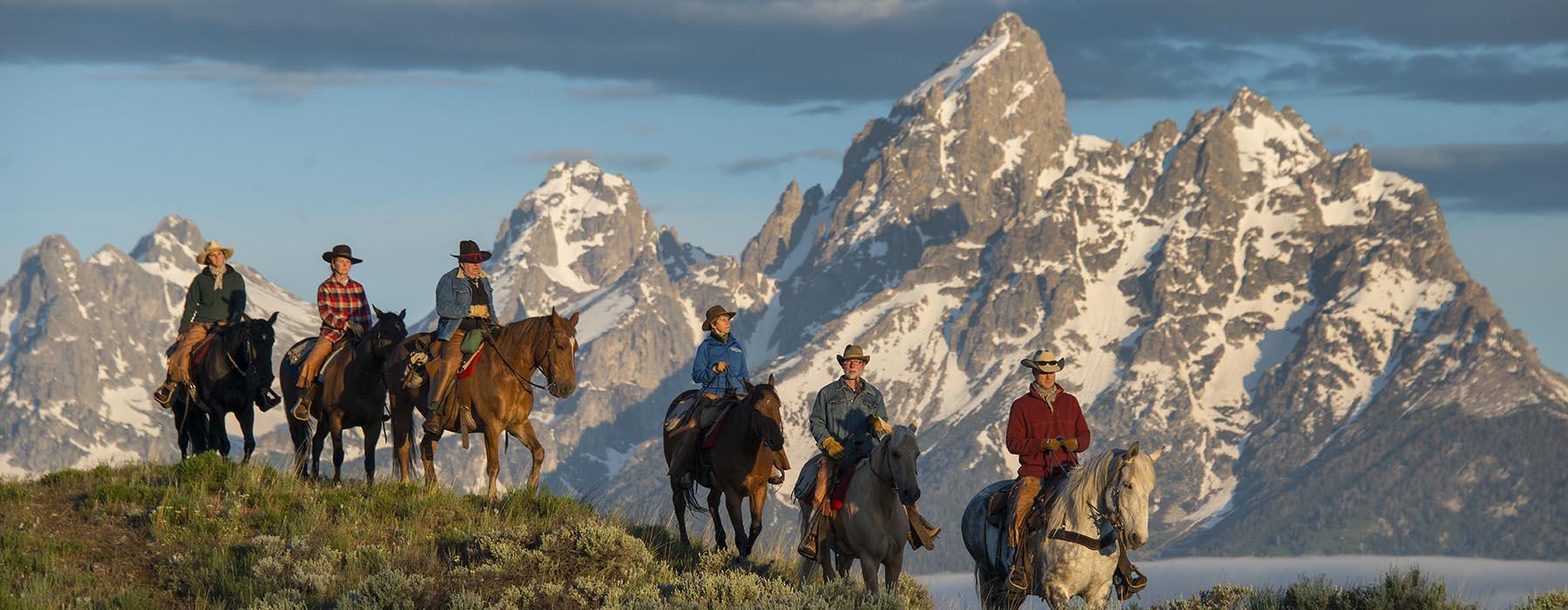 Horseback riders overlooking mountains.